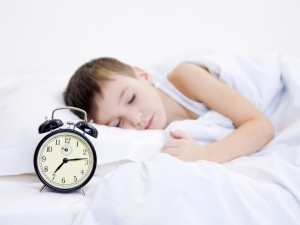 Little boy sleeping with alarm clock near his head